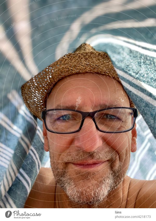 Beach life under a beach towel Man portrait Contentment Adults Looking Straw hat Designer stubble Eyeglasses Person wearing glasses Human being 1