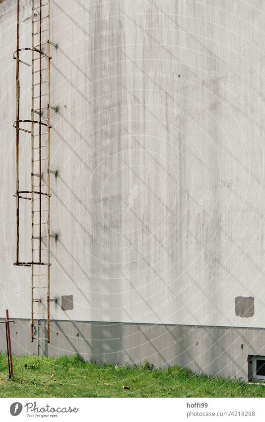 Shadow cast by an external conductor on a grey wall rusty escape ladder Ladder Escape route shadow cast Warehouse Harbour Facade Industry Industrial Photography