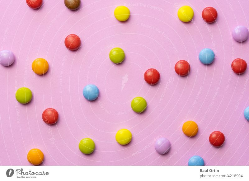 Colorful chocolate candies smarties background.Top view sweets multicolored food texture, on pink background. colorful candy confectionery balls eat bonbons