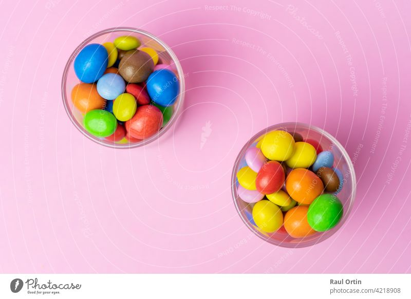 Multicolored chocolate candies in glass jar on blue vintage wooden background.Top view colorful sweets background concept with copy space for text. candy balls