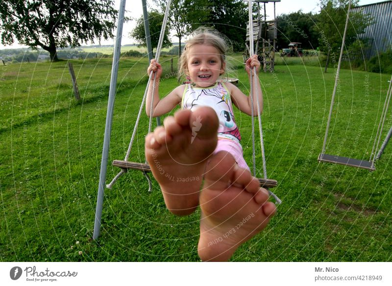 Girl swinging barefoot in the garden To swing Toddler Infancy Playing Swing Playground Movement Joie de vivre (Vitality) fun Smiling Laughter Summer Garden