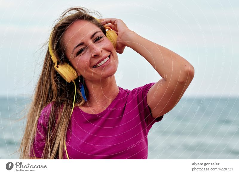 young woman at the beach hearing music with yellow headphones summer beautiful ocean nature girl sea hat relaxation lifestyle female outdoor people sky