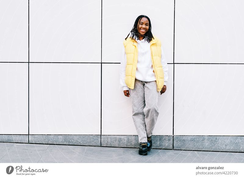 Woman smiling while leaning on street wall. che portrait woman african american urban black outdoors standing style city braids hairstyle clothing afro one