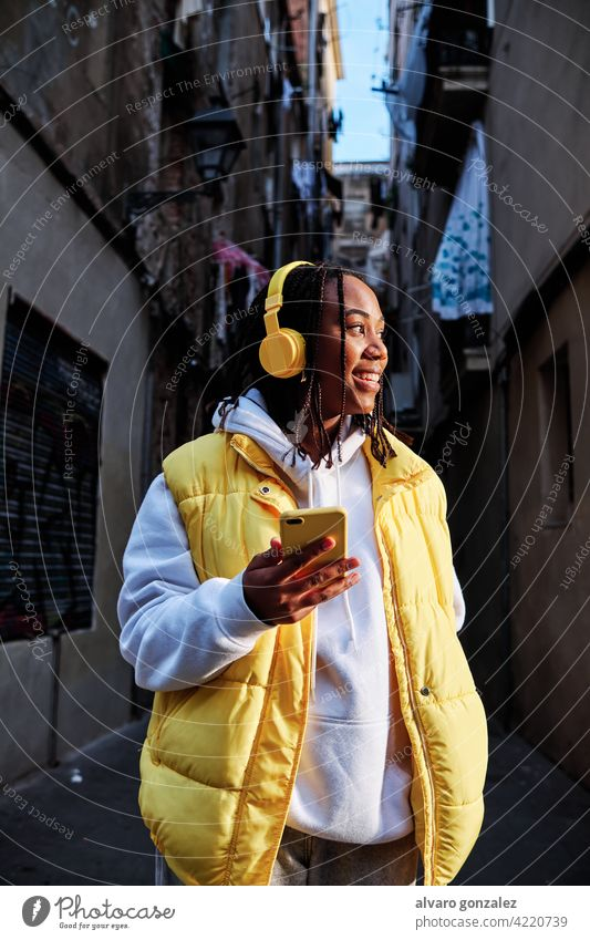 Woman listening music with headphones and phone. woman che mobile urban device enjoying technology outdoor african american wireless female outdoors smartphone