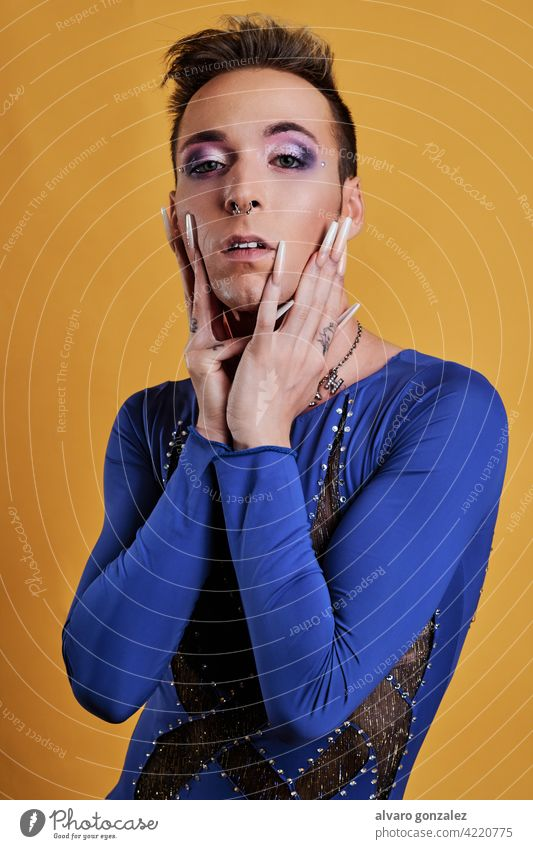 young transgender model with yellow background a blue dress che homosexual diversity feminine portrait guy make-up male person caucasian isolated white makeup