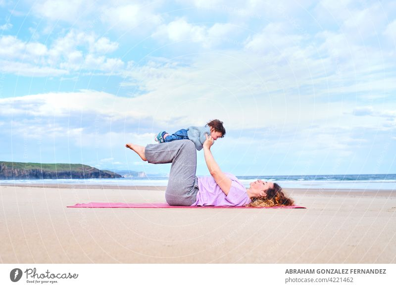 mother holds her baby on her lap while practicing yoga on a beach pilates exercise woman healthy child fitness relaxation meditation toddler wellness
