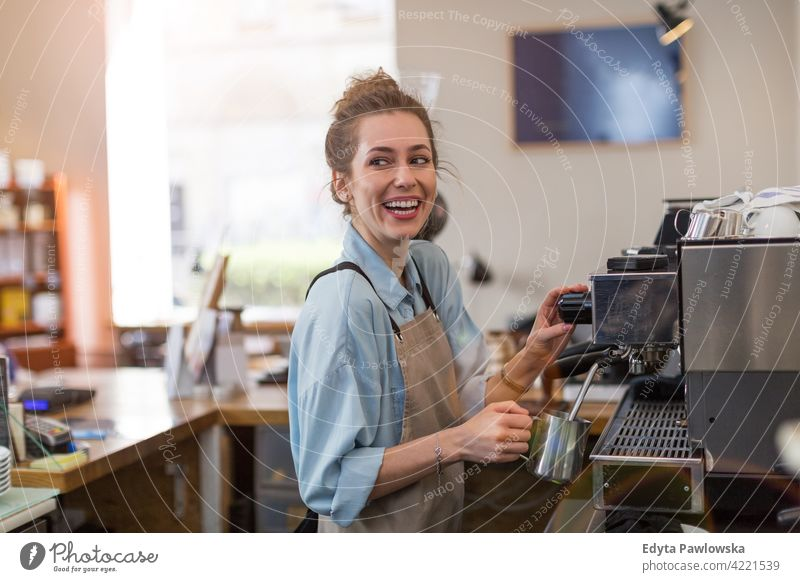 Female barista making coffee people woman young adult casual attractive female smiling happy indoors Caucasian toothy enjoying cafe restaurant apron business
