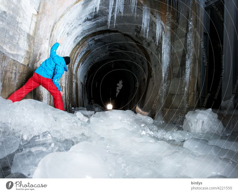Ice and frost, but light at the end of the tunnel. Man looks into a tunnel in the mountains, frozen thaw water Tunnel Icicle Cold Winter