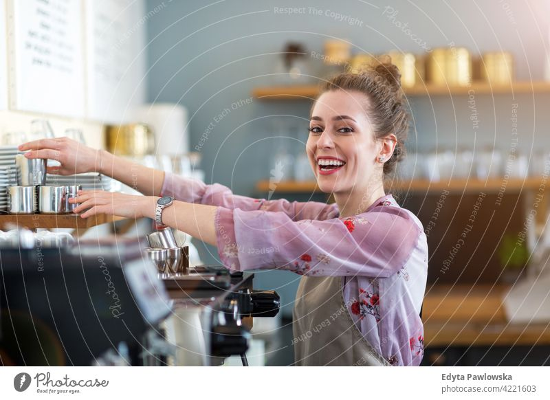 Young woman working in coffee shop people young adult casual attractive female smiling happy indoors Caucasian toothy enjoying cafe restaurant apron business