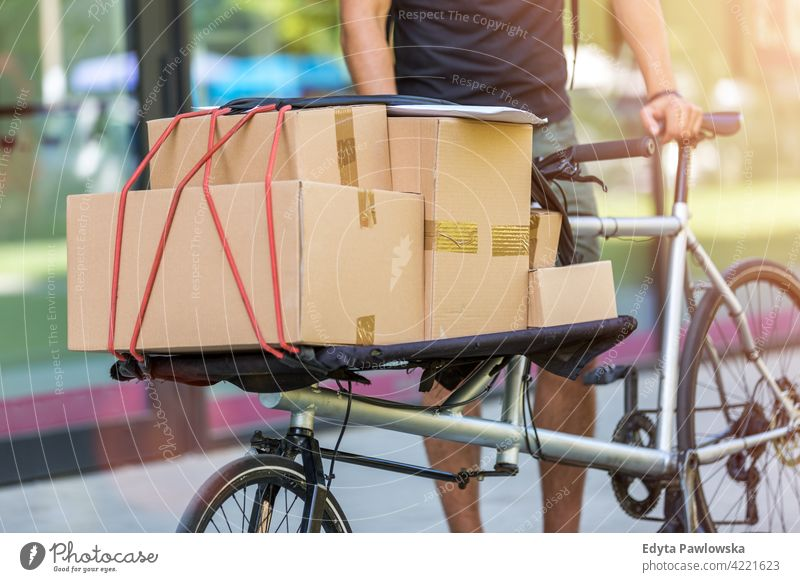 Bike courier making a delivery people young adult man male smiling happy blue collar Courier dispatch rider delivery man delivering package packages boxes