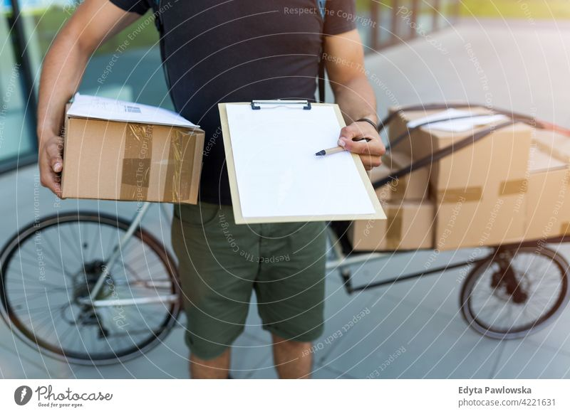 Courier with clipboard and cardboard boxes people young adult man male smiling happy blue collar dispatch rider delivery man delivering package packages parcel