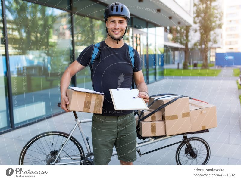 Bicycle messenger making a deliveryon a cargo bike people young adult man male smiling happy blue collar Courier dispatch rider delivery man delivering package