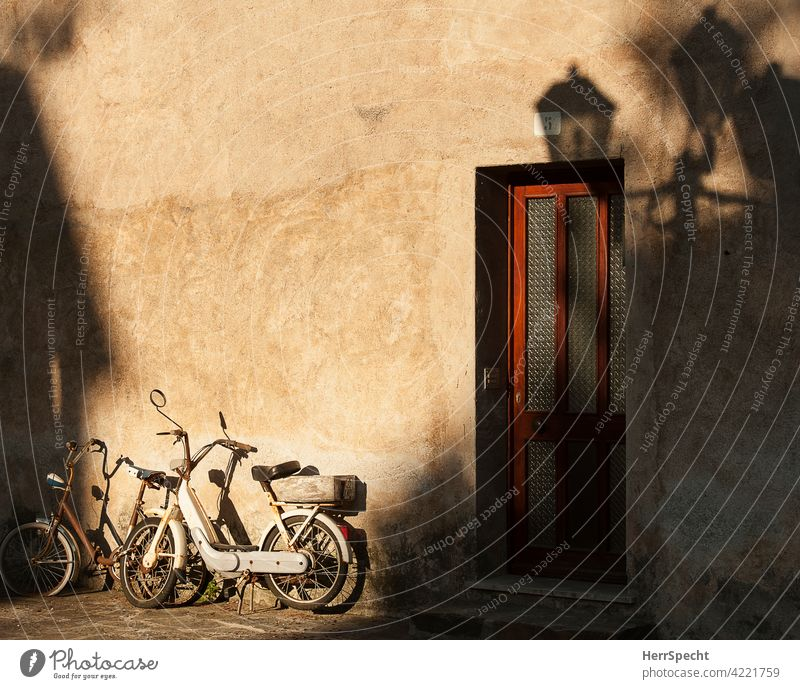 Bike and moped on house wall in the morning sun in Italy Bicycle Mofa Shadow play Exterior shot Motorcycle Building House (Residential Structure) Parking