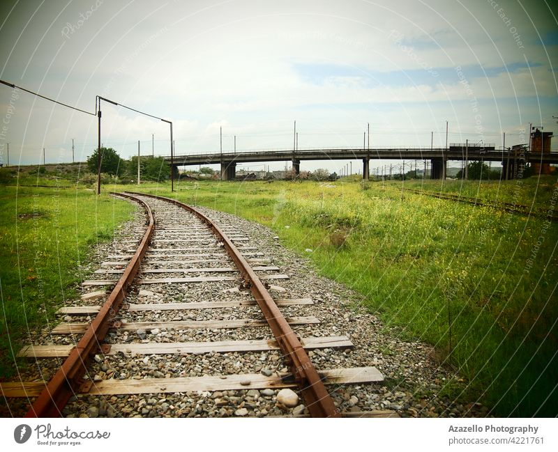 An old railway and a bridge with lomography effect railroad metal iron wood stone pebble gravel green grass transportation vintage retro train wagon carriage