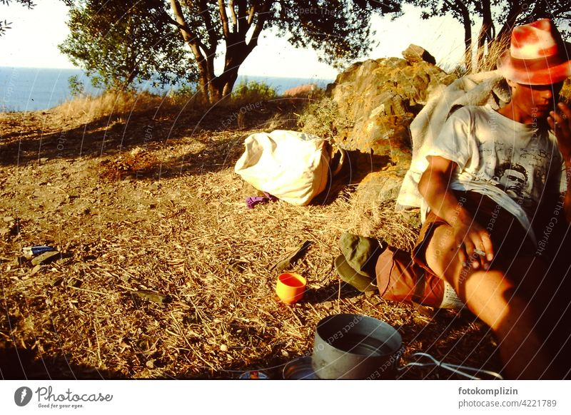 cool young man sitting on the ground in the nature and smoking globetrotters travelers simple life Traveling time-out relaxed Trip Mobile home feel free
