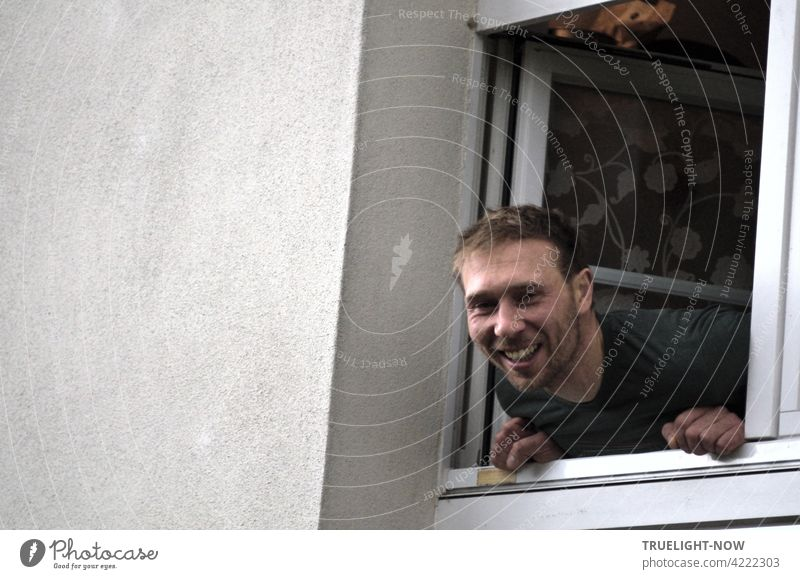 The friendliest neighbor ever - a young man and father leans out of a small window laughing and looks directly into the spontaneously drawn camera of the photographer