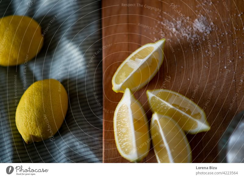 Full lemons and half lemons on a cutting board quarter lemons Cutboard Cut lemon Lemon and sugar Lemons Fruit Yellow Sour Fresh fruits Citrus fruits