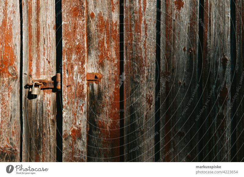Barn door locked Barn Door Lock closed door Padlock peeled off flaking paint Wooden gate Weathered weathered wood weathering Old Decline Derelict