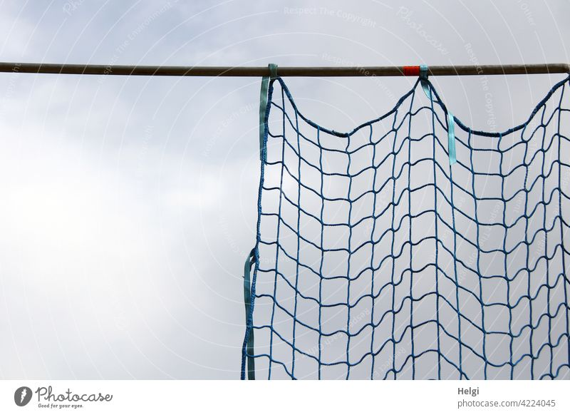 safety net pushed to the side for protection on a construction site in front of a blue-grey sky Net Network Backup Construction site pole Metal Metal post Sky
