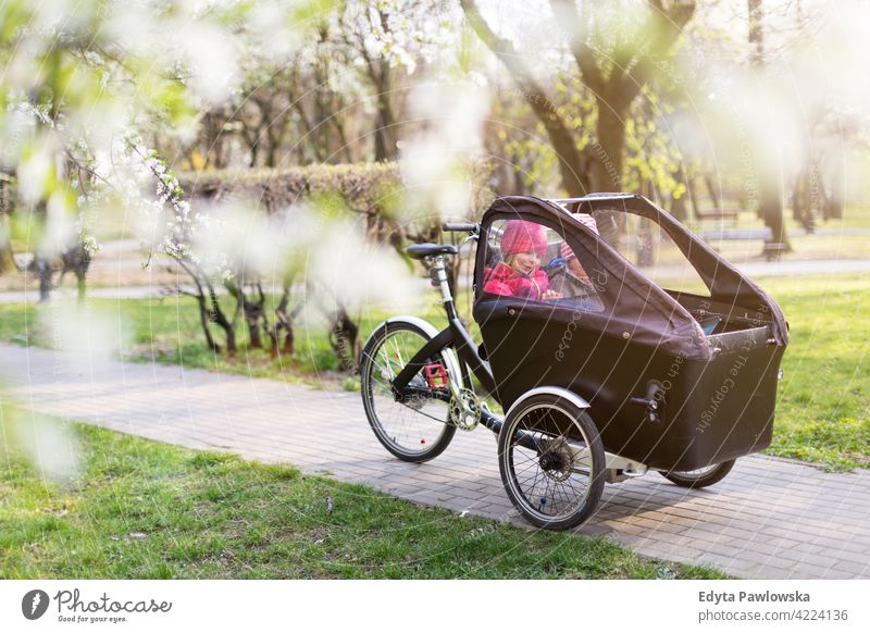 Children having a ride in a cargo bike during spring tricycle day healthy lifestyle active outdoors fun joy park bicycle biking activity cyclist enjoying