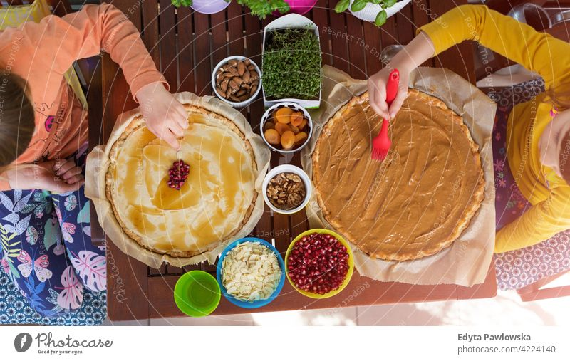 Little girls decorating mazurek (Polish Easter cake) table decoration hand food kitchen cooking family home eating meal healthy preparing baking colorful