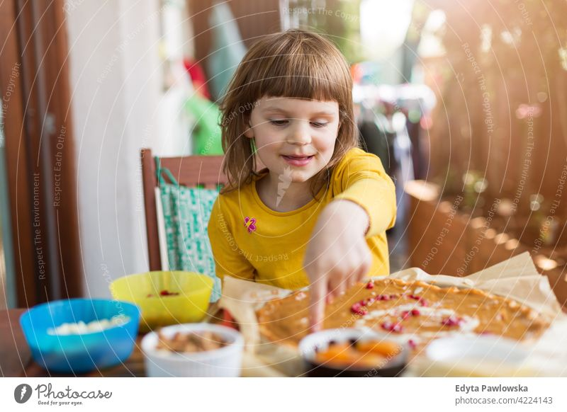 Little girl decorating mazurek (Polish Easter cake) table decoration hand food kitchen cooking family home eating meal healthy preparing baking colorful