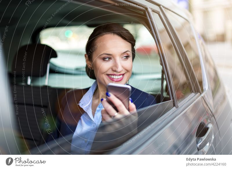 Young woman with smartphone on the back seat of a car carsharing confident smiling satisfaction female attractive beautiful young adult joy positive content