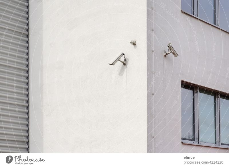 Two surveillance cameras are mounted on the corner of a functional building with windows and a roller shutter door / Security technology / Surveillance