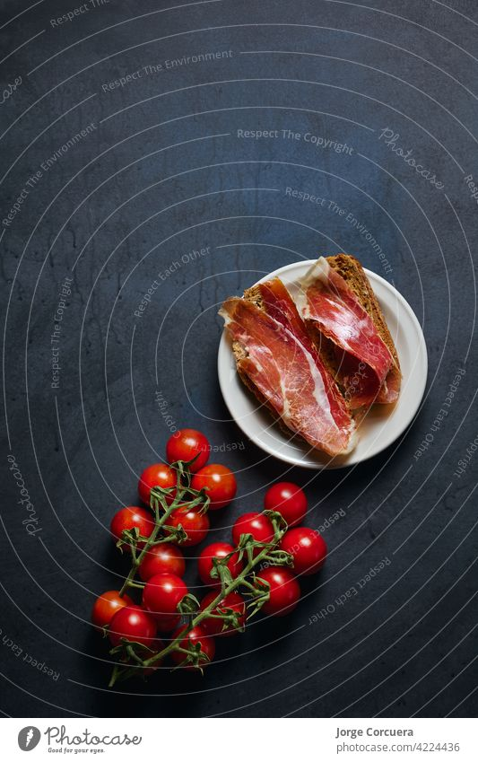 dish with Iberian ham with copy space for advertising toast serrano cured pork meat prosciutto toasted meal slice spanish tomato sliced iberian lunch tapas