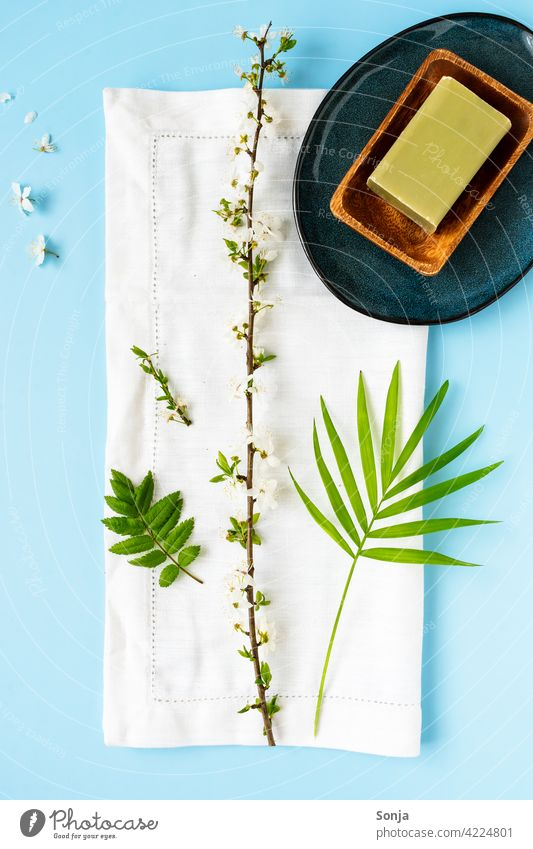 A green soap in a wooden bowl, a white towel and a flower branch on a blue background Soap Green flowering twig Towel Beauty Photography Wellness Spa Relaxation