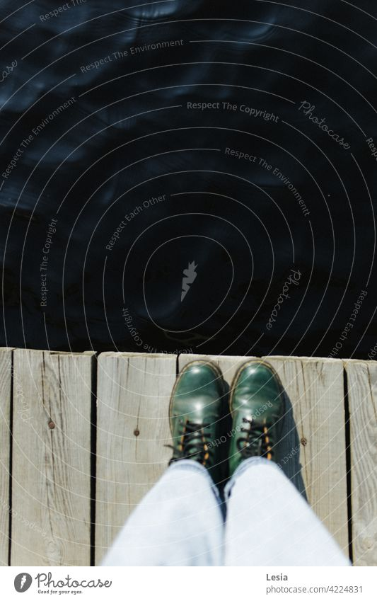 Green shoes! Boots swamp laces walk Bridge Water dark water dirty water get wet wet feet dry boots Jeans Stand to watch Pond