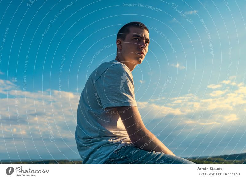 seated young man looks into the distance in a beautiful landscape sitting looking sky blue summer outdoor car sunset sundown nature sunlight sunbeam romantic