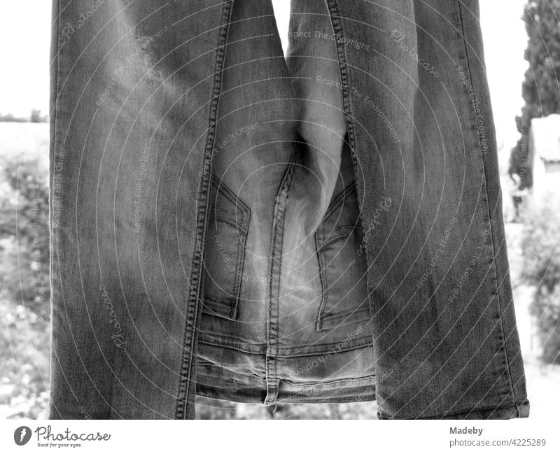 Old freshly washed jeans on the clothesline in a courtyard in the old town of Alacati near Cesme on the Mediterranean Sea in the province of Izmir in Turkey, photographed in neo-realistic black and white