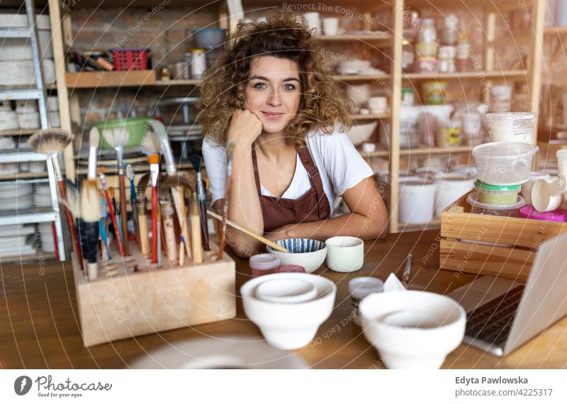 Portrait of woman pottery artist in art studio ceramics work working people young adult casual attractive female happy Caucasian enjoying one person beautiful