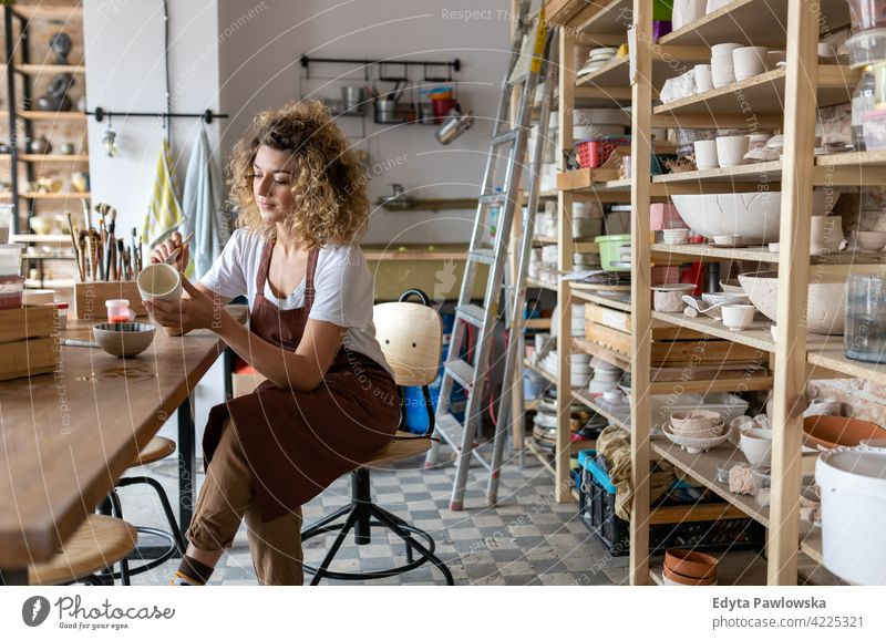 Craftswoman painting a bowl made of clay in art studio pottery artist ceramics work working people young adult casual attractive female happy Caucasian enjoying