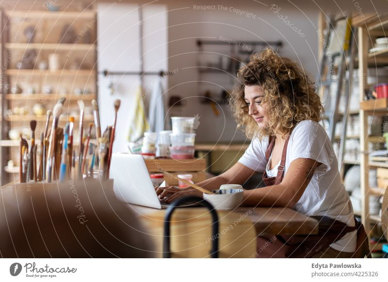 Woman pottery artist using laptop in art studio ceramics work working people woman young adult casual attractive female happy Caucasian enjoying one person