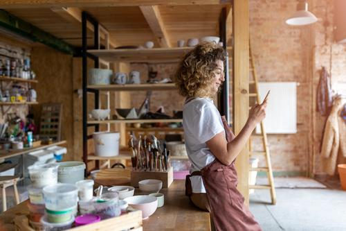 Female potter with smartphone in art studio pottery artist ceramics work working people woman young adult casual attractive female happy Caucasian enjoying