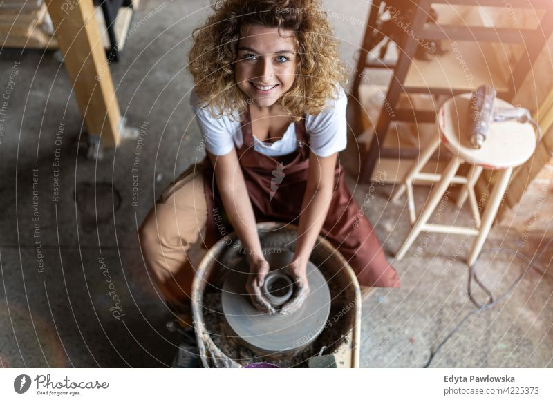 Woman making ceramic work with potter's wheel pottery artist ceramics working people woman young adult casual attractive female happy Caucasian enjoying