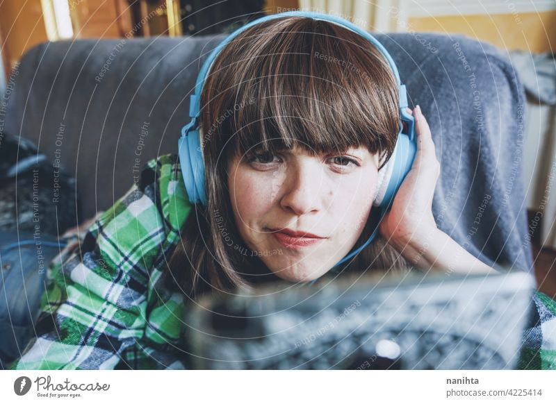 Young woman at home enjoying music indoor leisure technology phone smart phone device headphones young young woman youth teen teenager lifestyle real