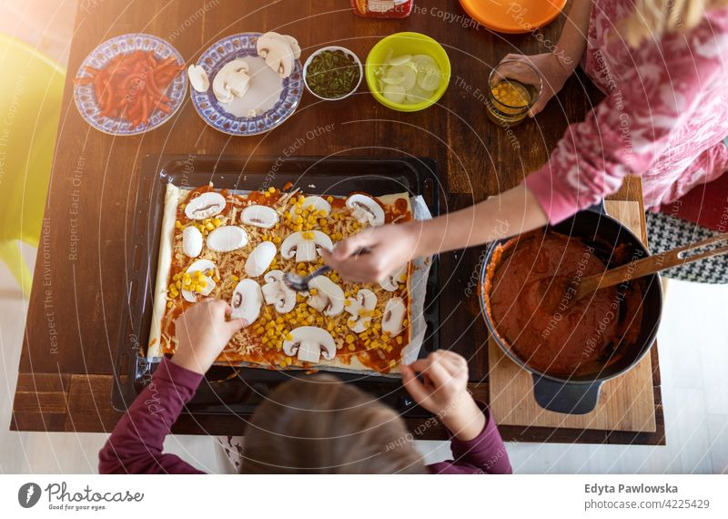 Children preparing pizza at home learning quality time spending time with family together kids childhood preparation food cheerful smiling girl people table