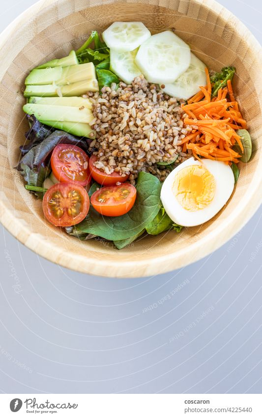 Brown rice salad with carrot, egg, cucumber, avocado, tomato and lamb's lettuce above antioxidant asian background bowl brown buddha bowl copy space cuisine
