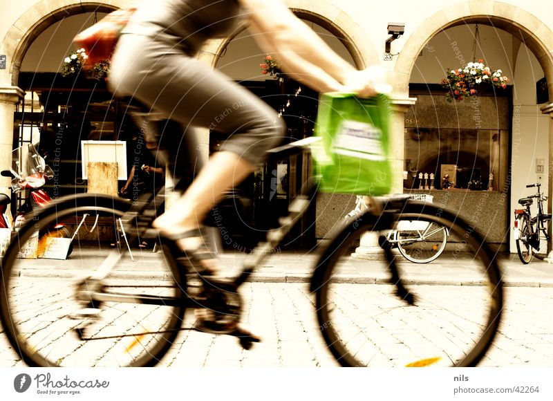 In the city Town Shopping Woman Downtown Middle Speed Mountain bike Paper bag Green Bicycle Transport Cobblestones Arcade Münster Old town Human being Dynamics