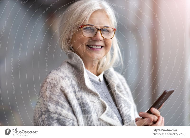 Portrait of senior woman using mobile phone glasses eyeglasses happy smiling enjoying relaxed positivity confident natural seniors pensioner pensioners casual