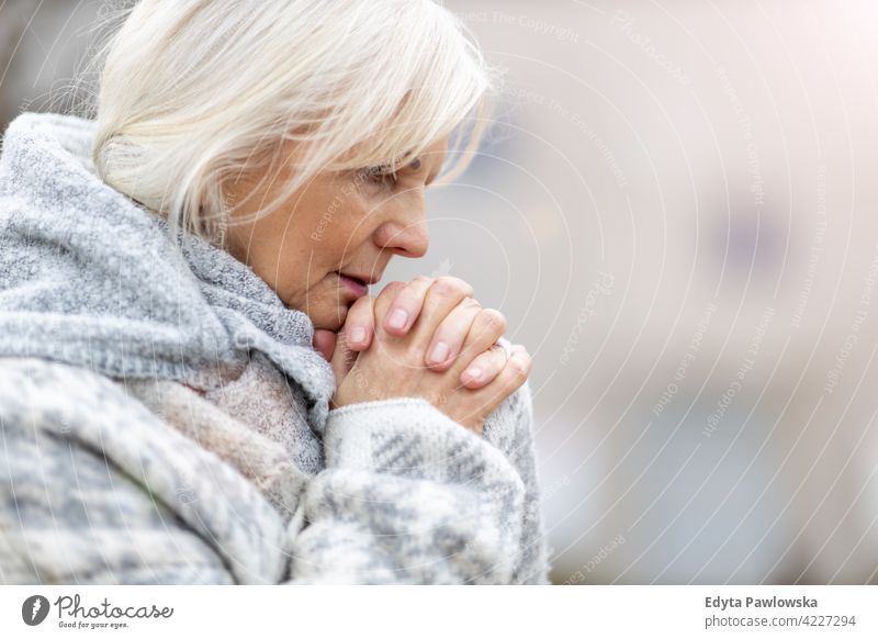 Portrait of senior woman praying hands wishing religion hope worried grief grieving depressed depression sad mourning seniors pensioner pensioners casual