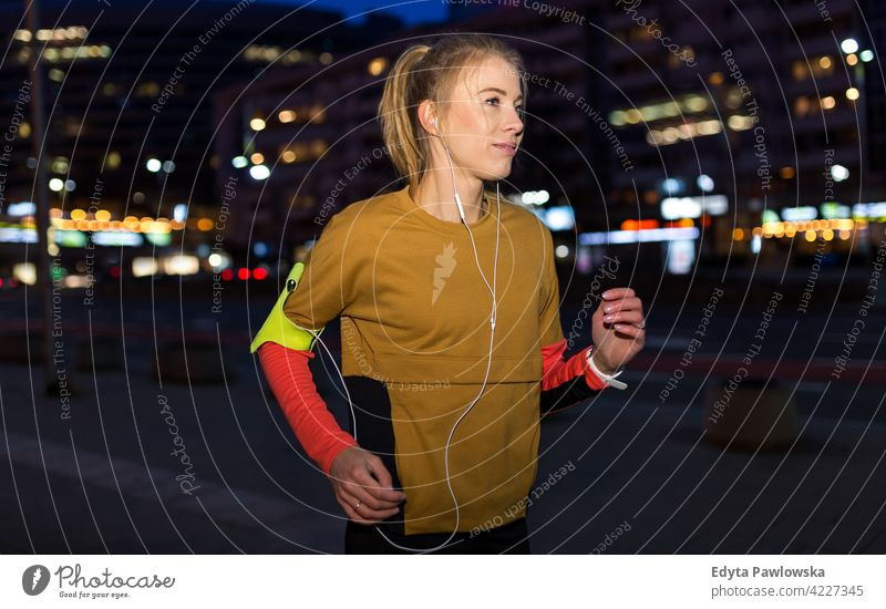 Female runner in city at night Jogger jogging running energy exercise clothing exercising fitness recreation sport activity vitality body gym clothes training