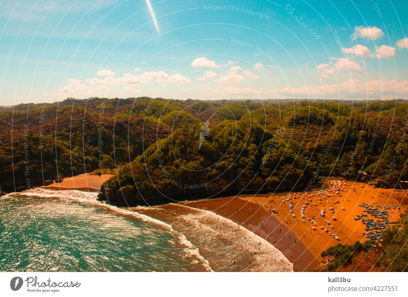 Lagoon beach Baron on Java Island in Indonesia, flanked from green mountains. lagoon sand parasols colorful swimming sea high angle view sitting people blue