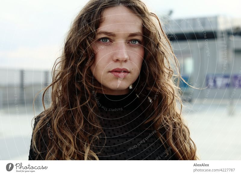Portrait of a young woman with long, brunette, curly hair on the top parking deck of a parking garage Woman Young woman 18 - 30 years pretty Beauty & Beauty