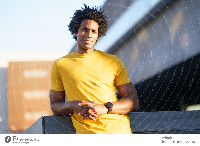 Black man with afro hair taking a break after workout. fitness black rest effort runner exercise jogger training male sport outside copyspace guy young park