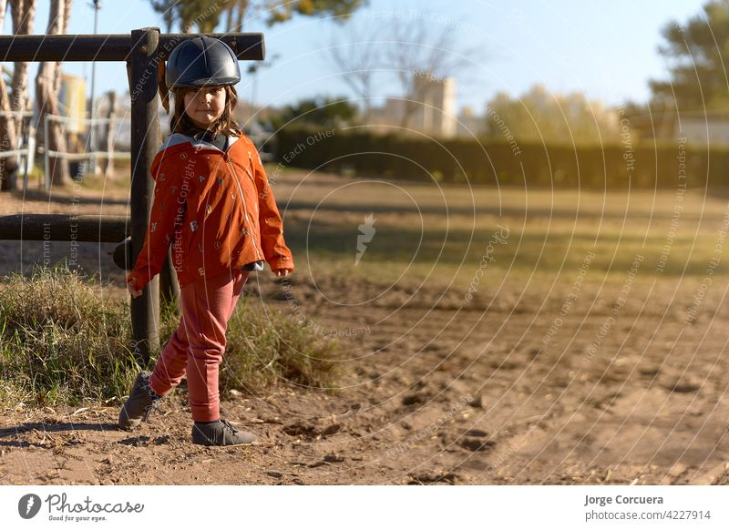 4 year old girl in horse riding dressed and ready to ride with nice posture and sunbeam. environment mixed between rural and urban animal beauty in nature cap