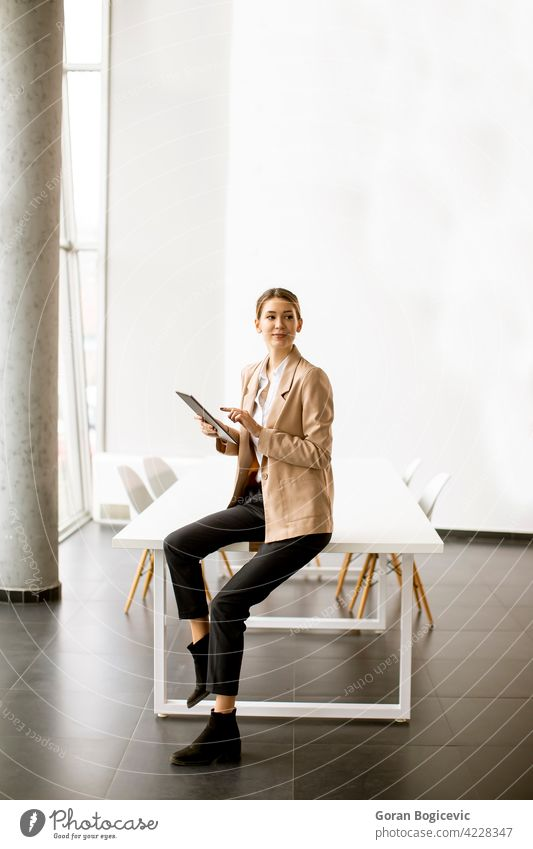 Young woman holding digital tablet in modern office adult attractive beautiful business businesswomen display electronic female happy indoors internet looking